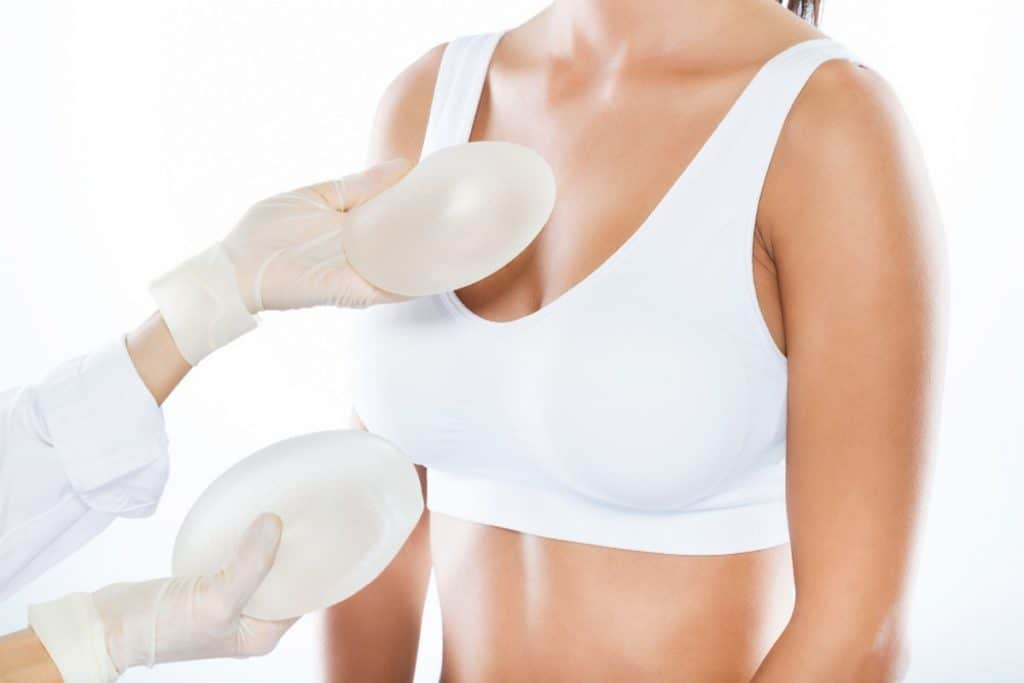 female doctor choosing mammary prosthesis with her patient white background